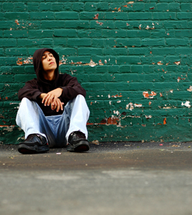 Homeless Youth Seated Against Wall